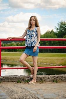 Vrouw in mouwloze blouse en spijkerrok die rust hebben op het recreatiegebied van het land, genietend van frisse lucht en rust