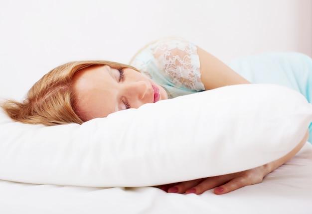 Vrouw in nachthemdslaap op wit hoofdkussen