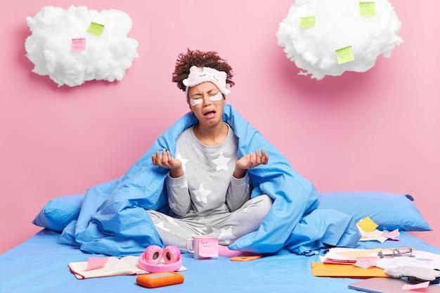 Vrouw in nachtkleding spreidt handpalmen en huilt van wanhoop kan moeilijke taak niet afmaken blijft in bed studeren in de verte werkt met papieren geïsoleerd op roze