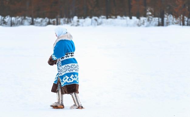 Vrouw in nationale kleding die door de sneeuw loopt. vakantie van de dag van de rendieren noordelijke volkeren.