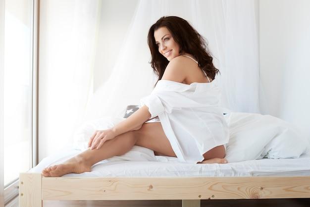 Vrouw in ondergoed in de slaapkamer