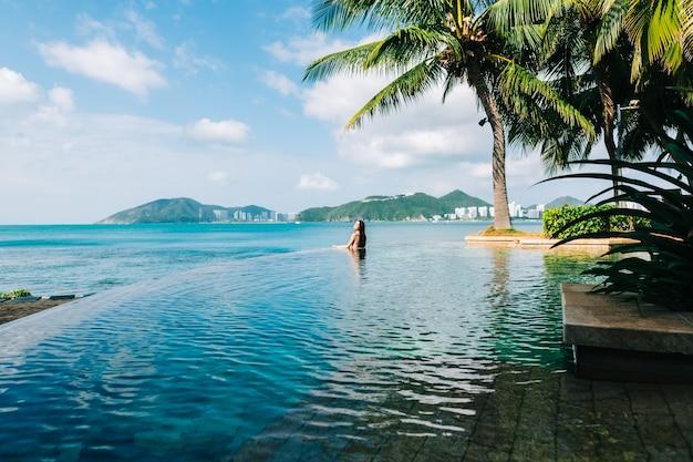 Vrouw in oneindig zwembad op prachtige tropische baai