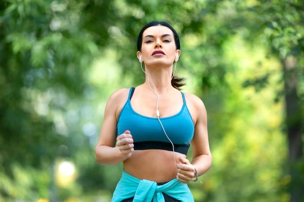 Vrouw in oortelefoons loper traint in het park