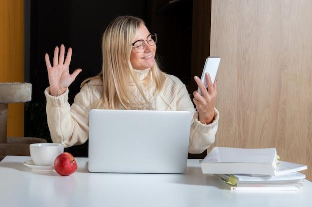 Vrouw in oortelefoons met behulp van mobiele telefoon tijdens het werken met laptop thuis keuken, online levensstijl werken
