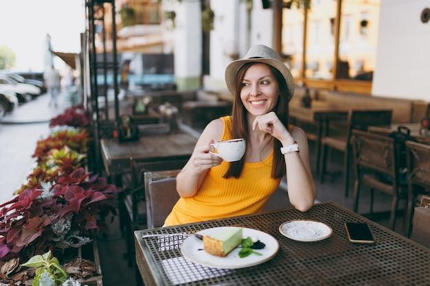 Vrouw in openlucht straat coffeeshop café zittend aan tafel in gele kleding hoed met kopje cappuccino, cake, ontspannen in restaurant tijdens vrije tijd