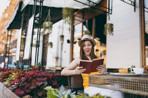Vrouw in openlucht straat coffeeshop café zittend aan tafel in hoed, leesboek met kopje cappuccino, cake, ontspannen in restaurant tijdens vrije tijd