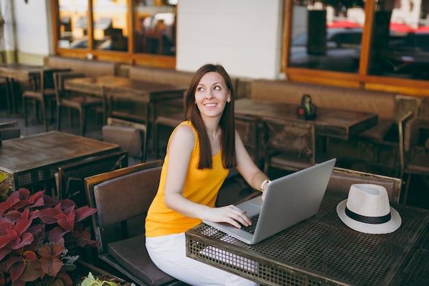 Vrouw in openlucht straat coffeeshop café zittend aan tafel werken op moderne laptop pc-computer, ontspannen in restaurant tijdens vrije tijd