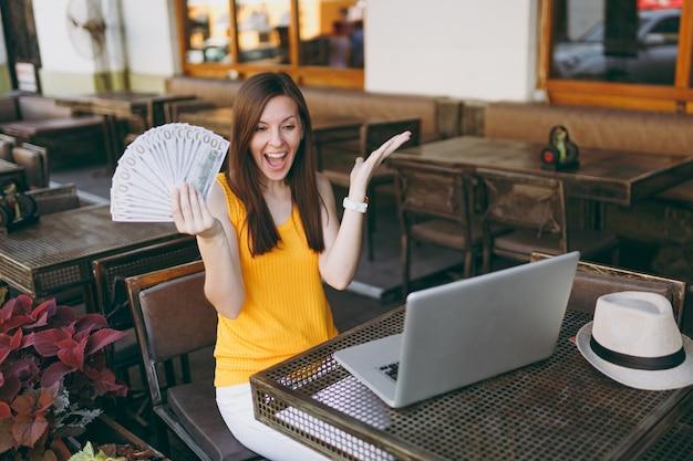 Vrouw in openlucht straat coffeeshop café zittend met moderne laptop pc-computer, houdt in de hand een stel dollars bankbiljetten
