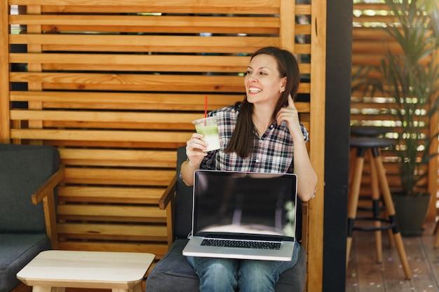 Vrouw in openlucht straat coffeeshop houten café zittend in vrijetijdskleding, laptop pc-computer met leeg leeg scherm vasthouden, ontspannen in vrije tijd. mobiel kantoor