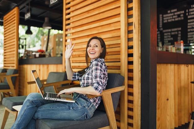 Vrouw in openlucht straat zomer coffeeshop houten café zittend in vrijetijdskleding, werken op moderne laptop pc-computer