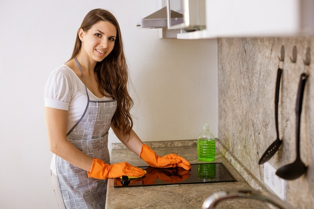 Vrouw in oranje handschoenen wast het fornuis met een doek