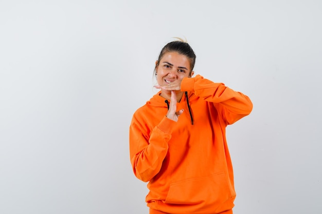 Vrouw in oranje hoodie die een gebaar van een pauze toont en er vrolijk uitziet