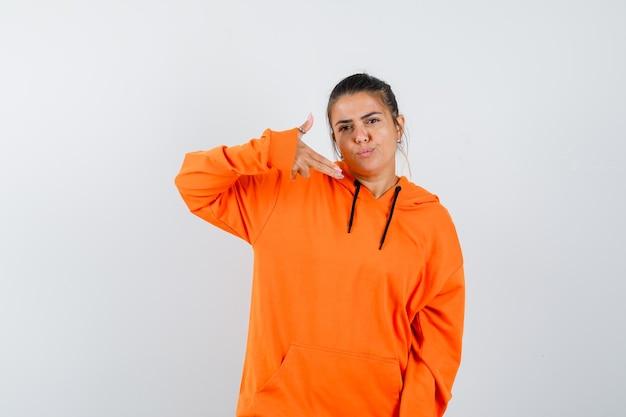 Vrouw in oranje hoodie die een pistoolgebaar toont en er zelfverzekerd uitziet