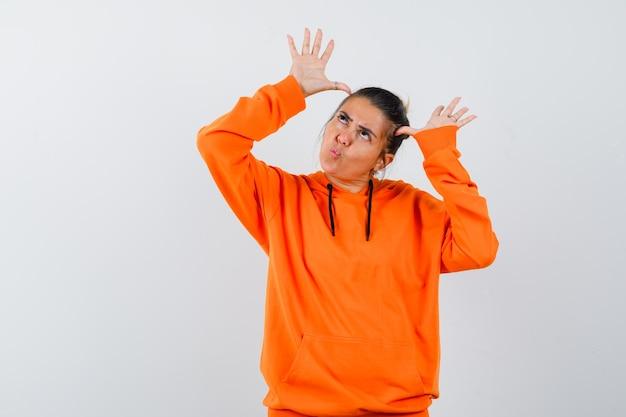 Vrouw in oranje hoodie die handen op het hoofd houdt als oren en er grappig uitziet