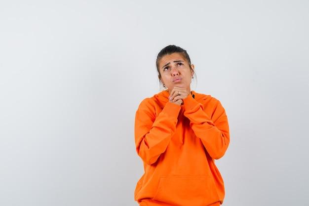 Vrouw in oranje hoodie die handen vastgrijpt in een biddend gebaar en er droevig uitziet