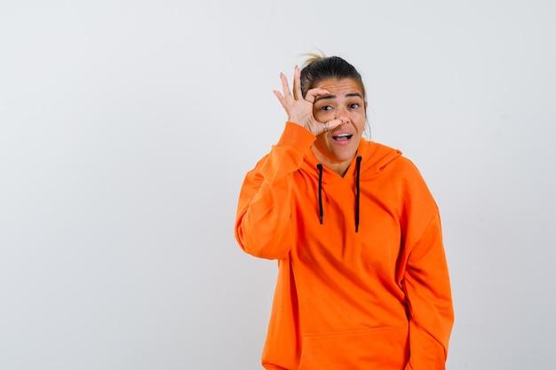 Vrouw in oranje hoodie die ogen opent met vingers en nieuwsgierig kijkt