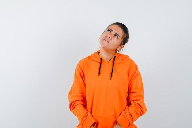Vrouw in oranje hoodie die opkijkt en aarzelend kijkt