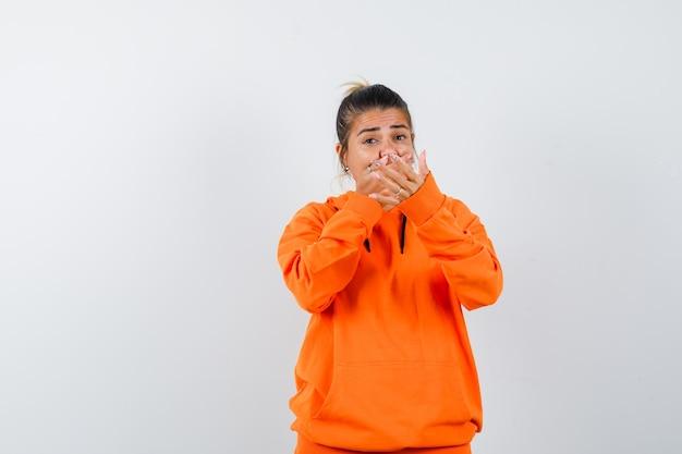 Vrouw in oranje hoodie die stopgebaar toont, hand op mond houdt en bang kijkt