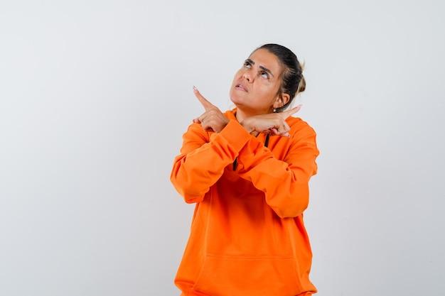 Vrouw in oranje hoodie die wegwijst en aarzelend kijkt