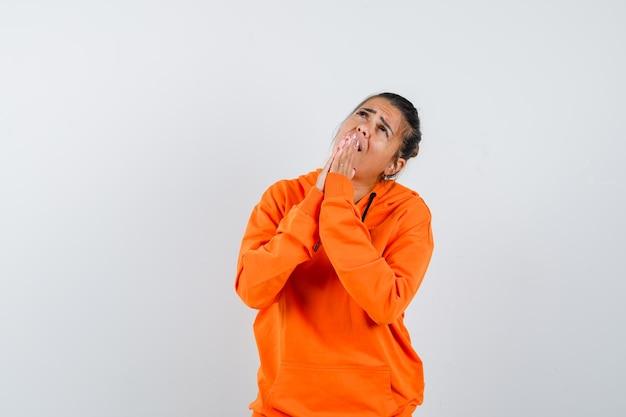 Vrouw in oranje hoodie houdt handen in gebedsgebaar en ziet er hoopvol uit