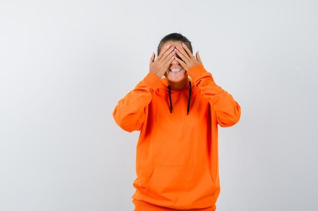 Vrouw in oranje hoodie houdt handen op ogen en kijkt opgewonden