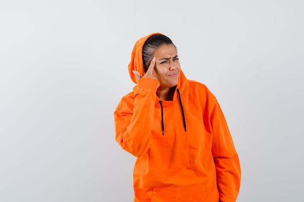Vrouw in oranje hoodie houdt vinger op slapen en ziet er zelfverzekerd uit