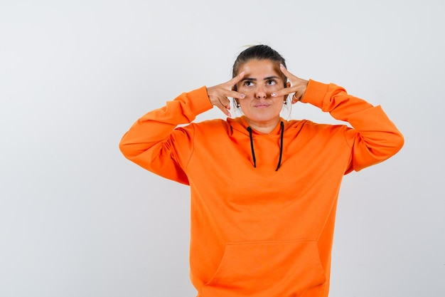 Vrouw in oranje hoodie met v-teken op ogen en aarzelend
