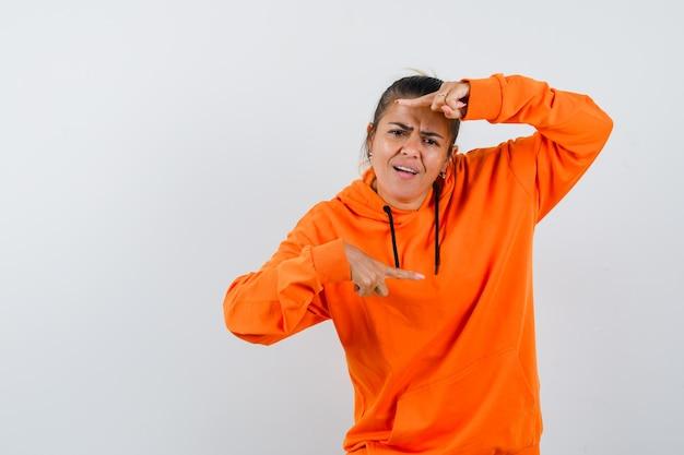 Vrouw in oranje hoodie wijst naar beide kanten en kijkt verward