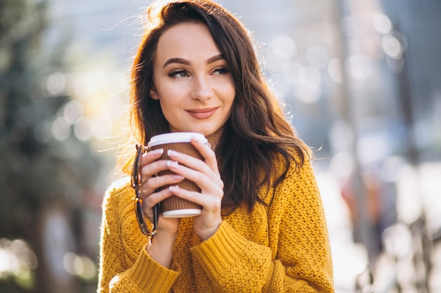 Vrouw in oranje trui koffie drinken