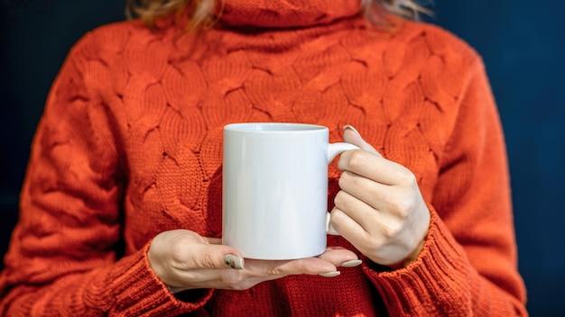 Vrouw in oranje trui met een witte beker met beide handen,
