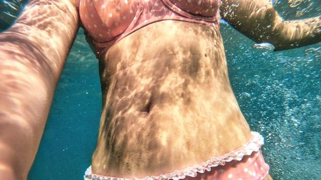 Vrouw in oranje zwembroek in het blauwe en transparante water van de middellandse zee. de camera vasthouden