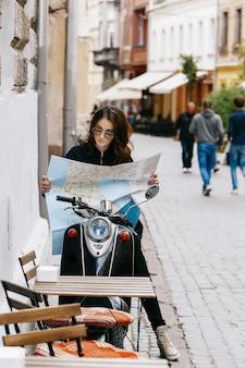 Vrouw in originele zonnebril zit op de scooter met toeristische kaart