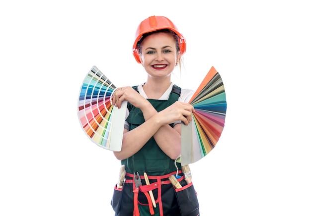 Vrouw in overall met kleurstaal geïsoleerd op een witte muur