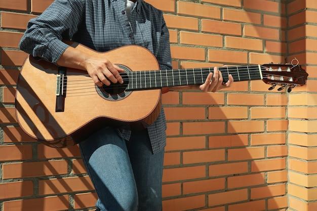 Vrouw in overhemd die op klassieke gitaar speelt