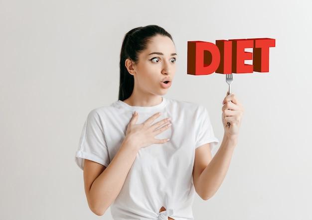 Vrouw in overhemd met de folk geïsoleerd op wit. vrouwelijk model met een bord met letters van het woord dieet. kiezen voor gezond eten, dieet, biologische voeding en een natuurvriendelijke levensstijl.