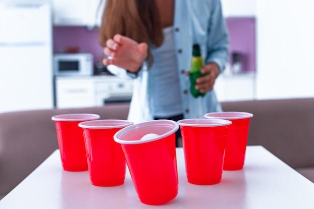 Vrouw in overhemd met dranken die pret hebben en van bier pong spel op lijst genieten thuis