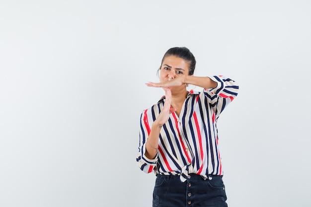 Vrouw in overhemd, rok die het gebaar van de tijdpauze toont en er zelfverzekerd uitziet