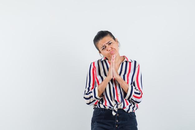Vrouw in overhemd, rok die namaste gebaar toont en nederig kijkt