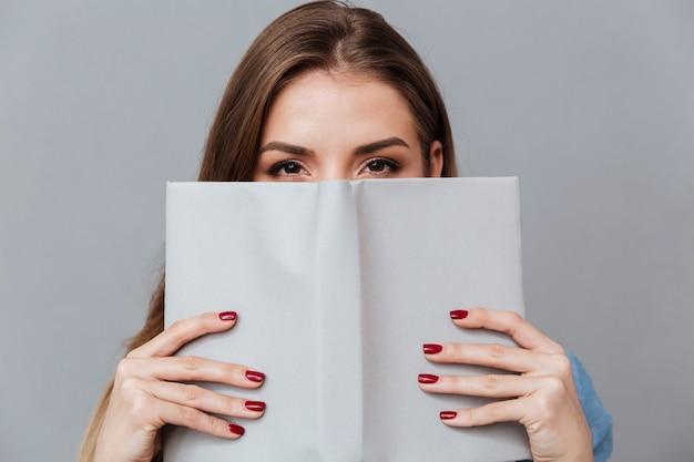 Vrouw in overhemd verstopt achter het boek