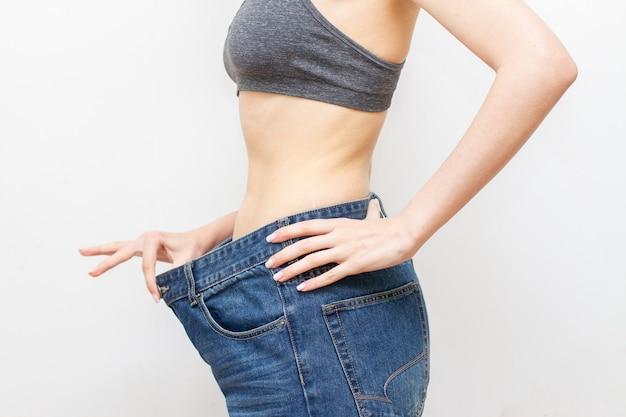 Vrouw in oversized broek na gewichtsverlies. dieet concept.