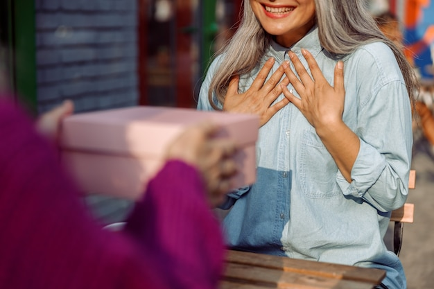 Vrouw in paars jasje geeft cadeau aan gelukkige grijsharige vriend die op het terras van een café zit