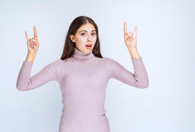 Vrouw in paars shirt met wolf oren teken.
