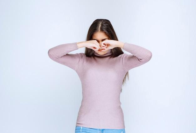 Vrouw in paars shirt voelt zich moe en slaperig.