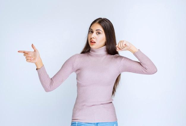 Vrouw in paars shirt wijzend op iets opzij.