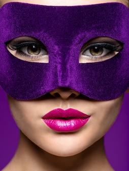 Vrouw in paars theatermasker op gezicht met violette lippen