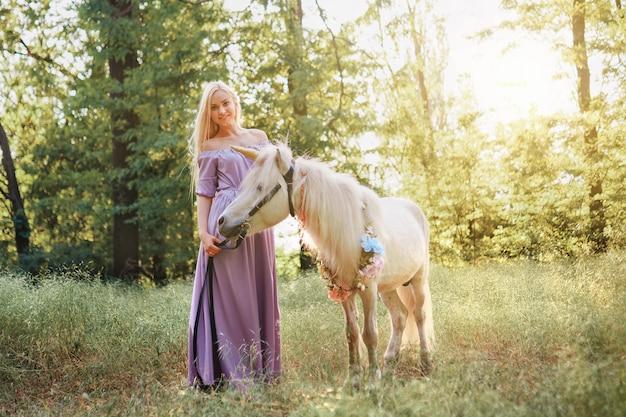 Vrouw in paarse jurk knuffelen witte eenhoorn paard. dromen komen uit. sprookje