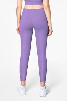 Vrouw in paarse sportbeha en legging activewear kleding full body