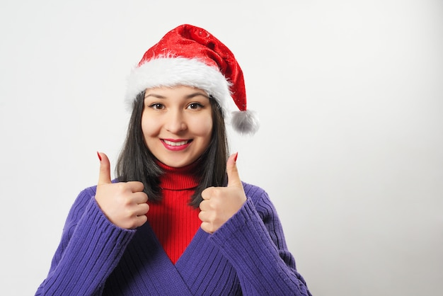 Vrouw in paarse trui en kerst hoed op witte achtergrond