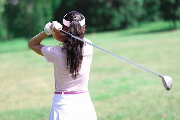 Vrouw in pak houdt golfclub achter haar rug