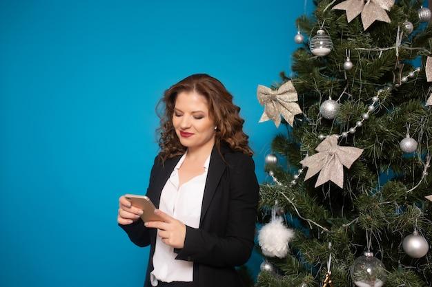Vrouw in pak met smartphone in de buurt van de kerstboom